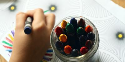 Child coloring with crayons next to a jar of assorted crayons.