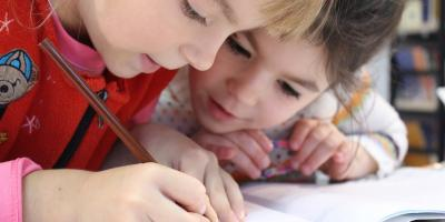 Two kids drawing with pencil