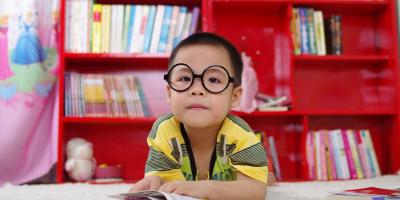 Child with glasses facing camera posed in front of a red bookshelf full of children's books.